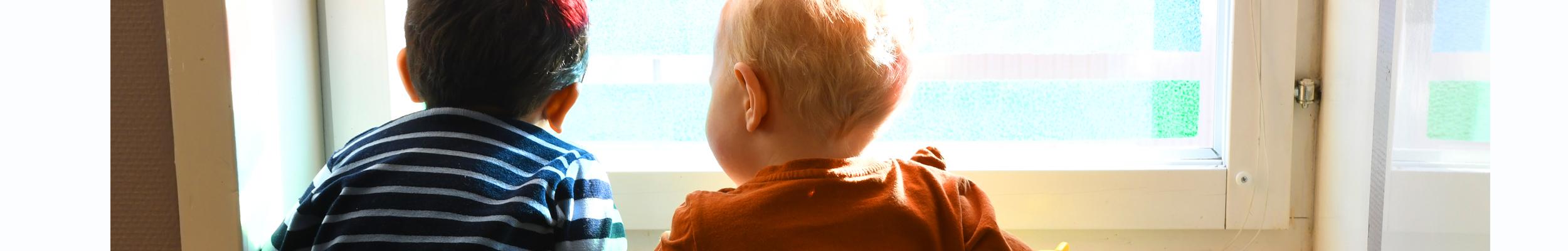 Två barn tittar ut genom fönstret